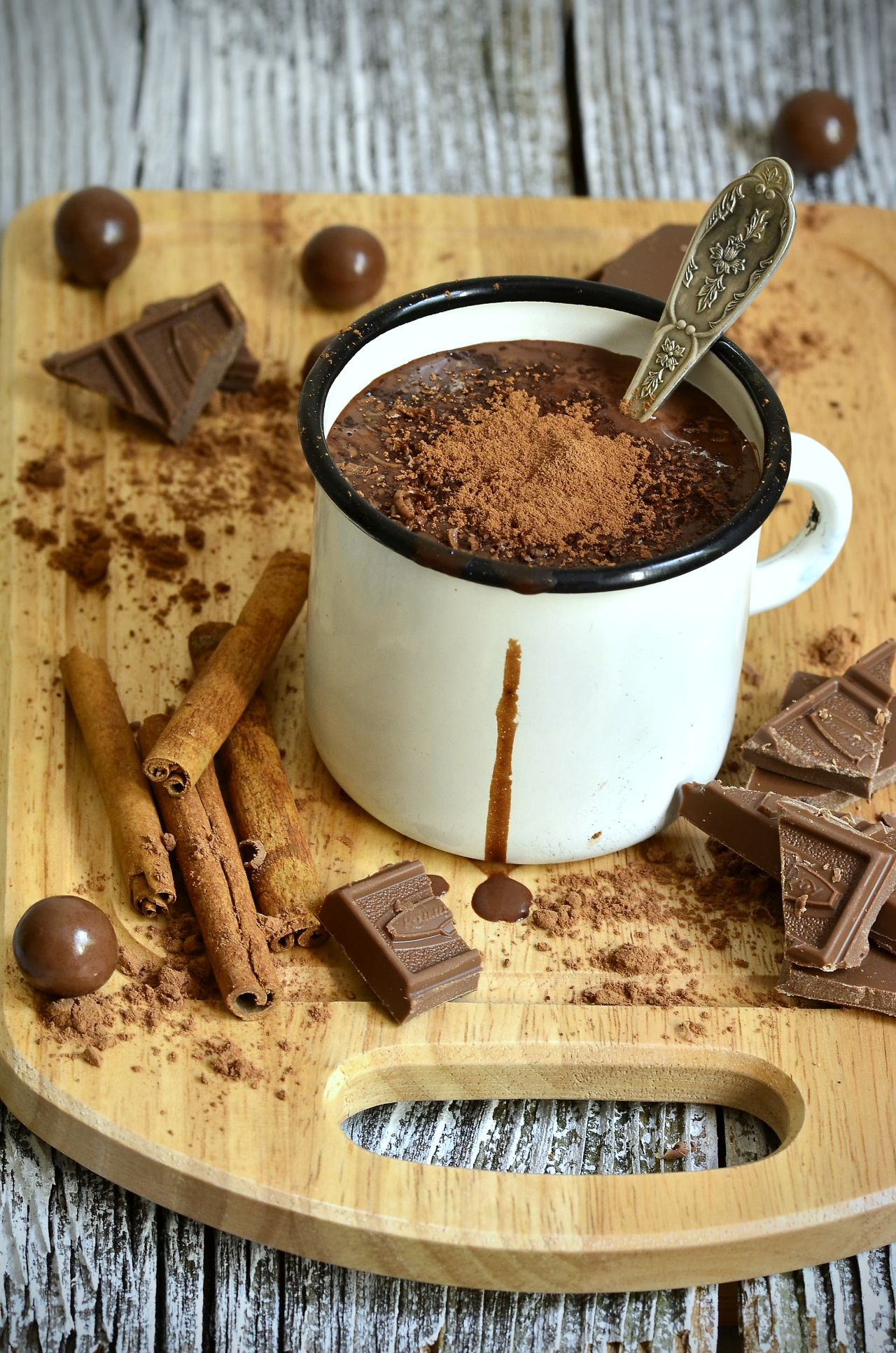 Hot chocolate in an enamel mug on the wooden board.