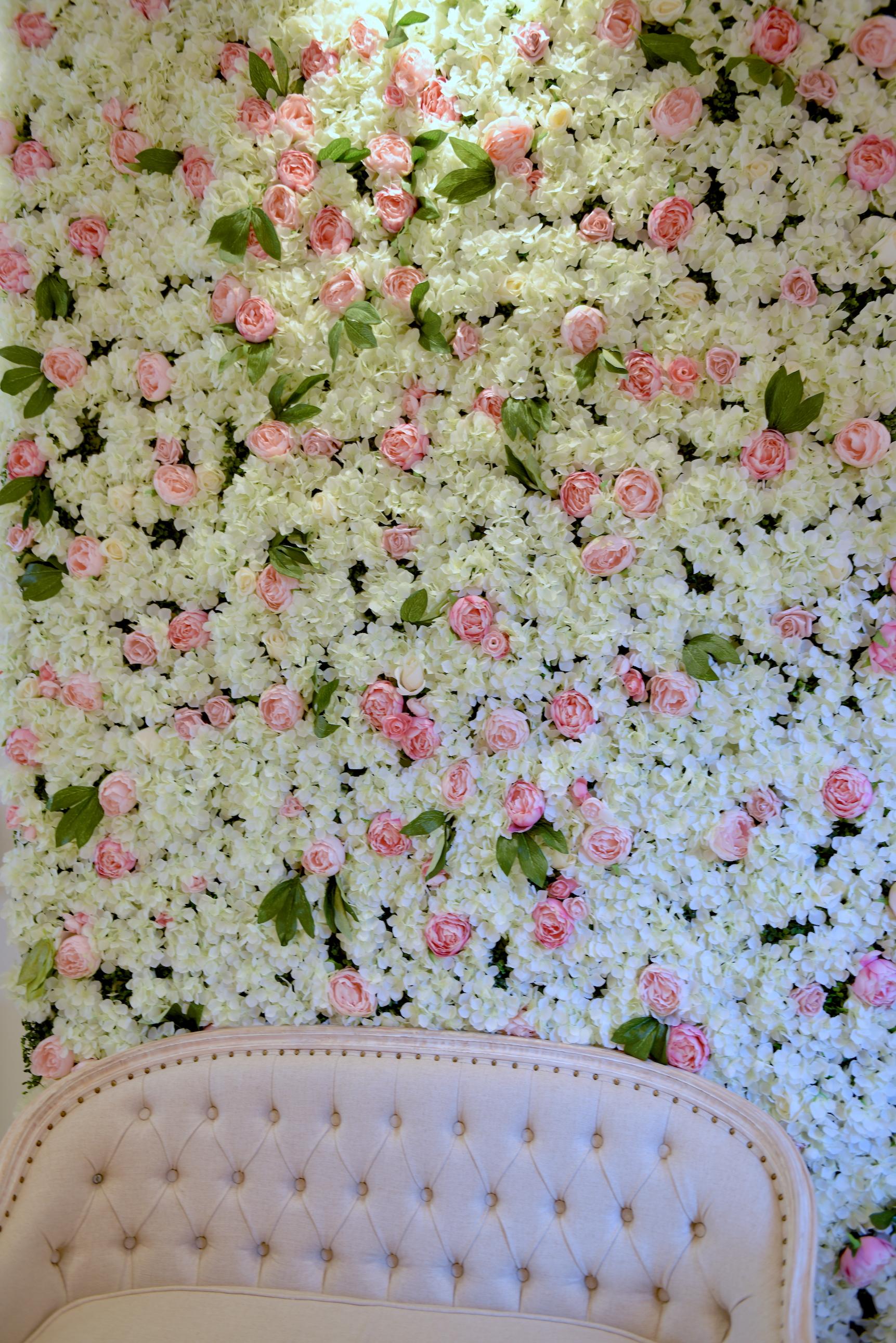 Pastelowa sofa z kolejną kwiatową ścianą w tle